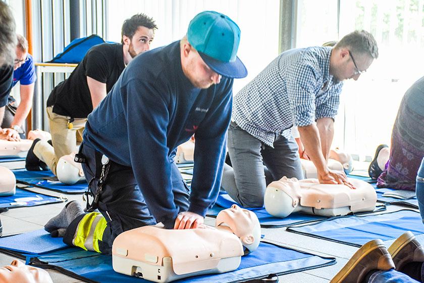 Anställda som deltar i HLR-utbildning och står på knä bredvid var sin docka och håller på med kompression av lungor
