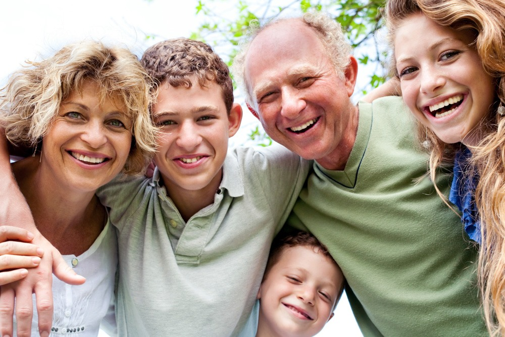Glad familj håller om varandra och tittat in i kameran