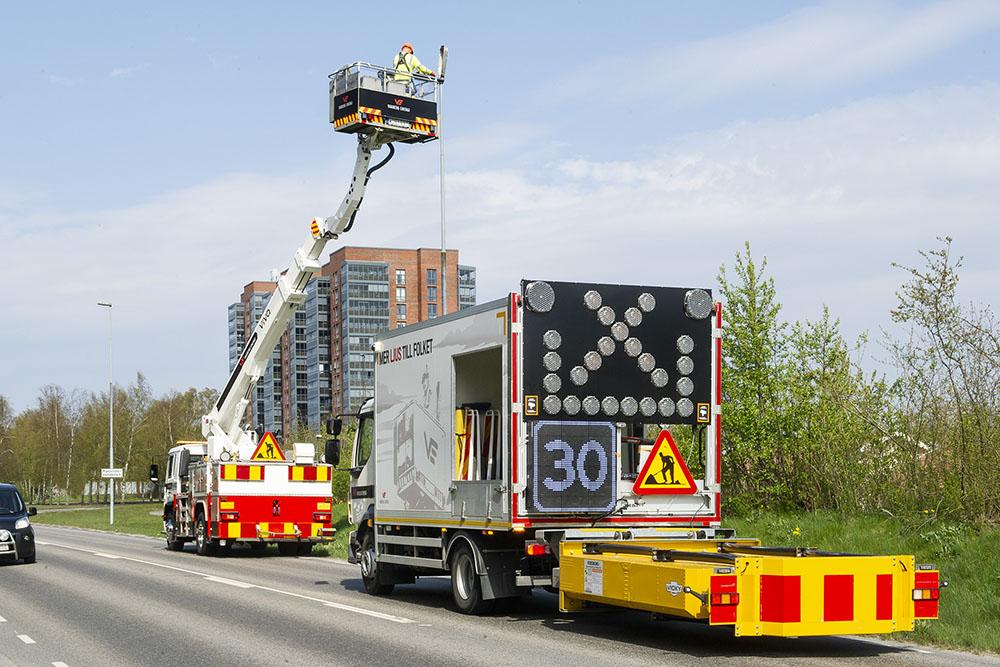 Gul TMA-bil samt en lastbil med skylift på rad i vägkanten med skylift och en arbteare i korgen som byter armatur i gatubelysningen