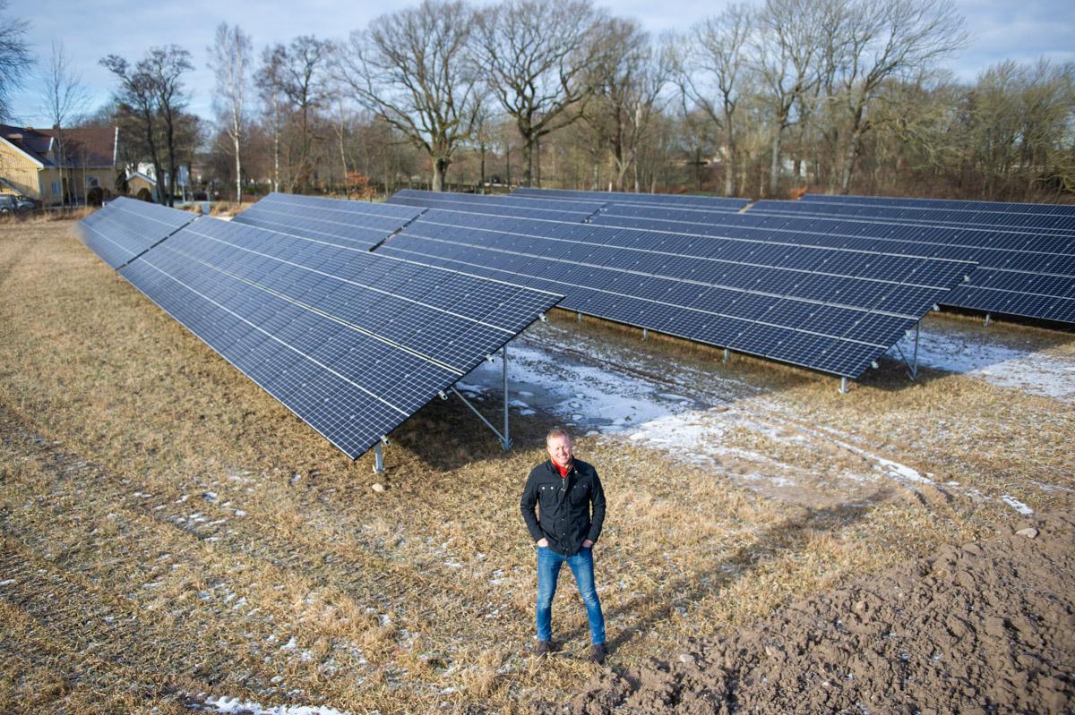 Anders Karlsson står bredvid en rad solceller