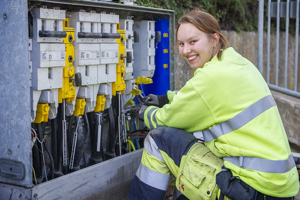 Maria Karlsson sitter i gula arbetskläder framför ett öppet kabelskåp och kopplar el