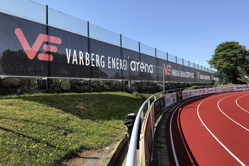 Stor reklambanner för varberg Energi uppsatt på Gunnnebo-stängsel i kurvan på Varberg Energi Arena