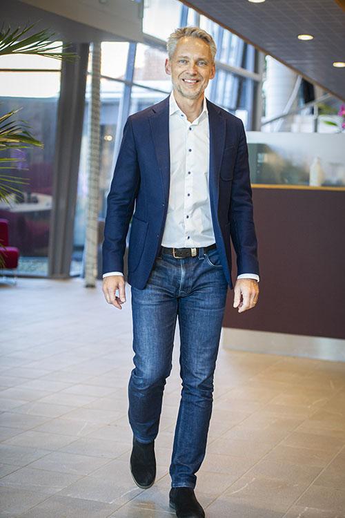 Vår VD Björn Sjöström går leende mot kameran vid receptionen iklädd blå kavaj, vit skjorta ococh blåjeans