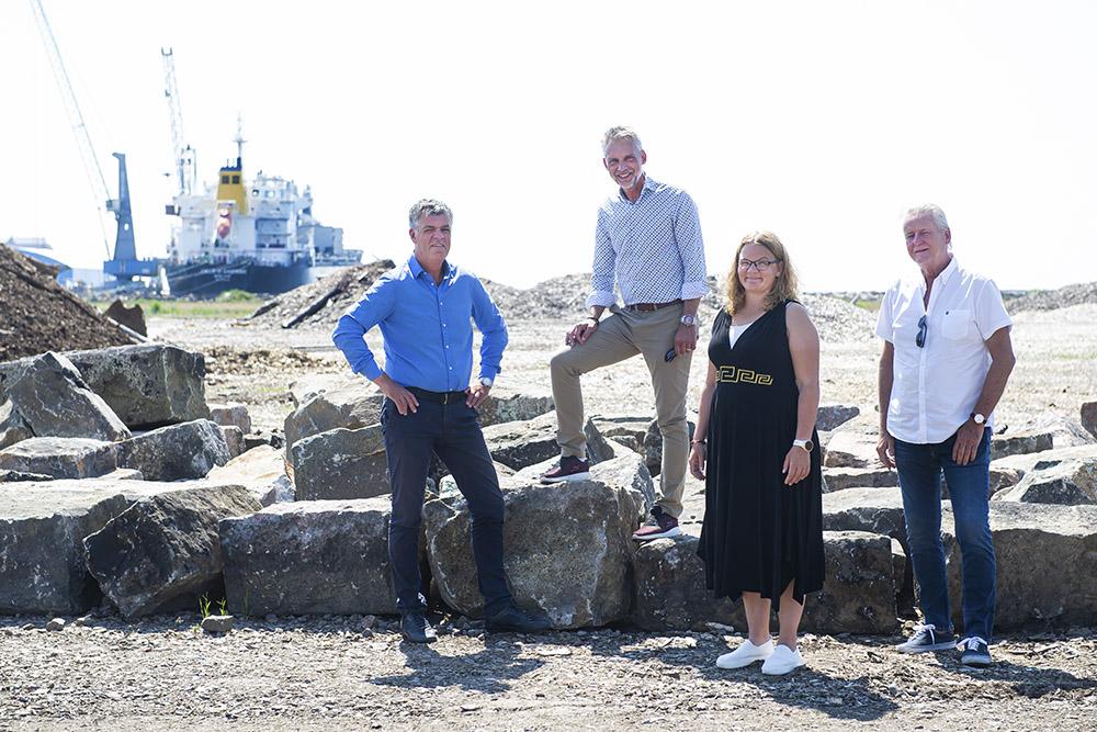 gruppbild med fyra personer i motljus framför ett lastfartyg som ligger i hamn