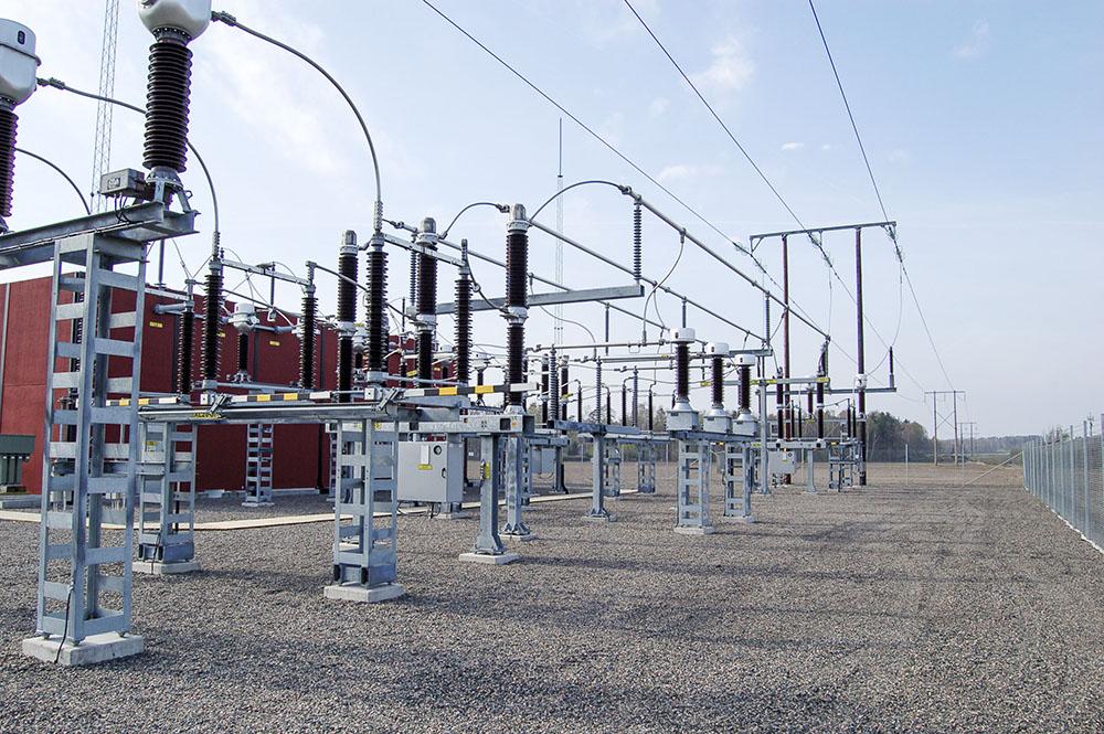 Transformatorstation med elstolpar och luftledningar
