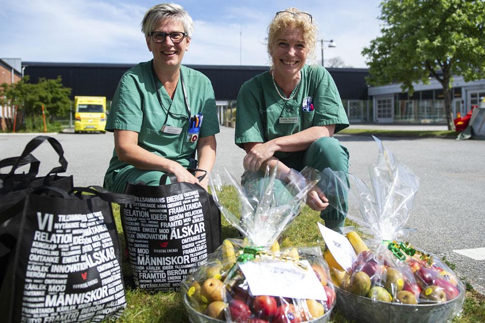 två sjuksköterskor sitter på huk framför akutingången tillsammans med två fruktkorgar