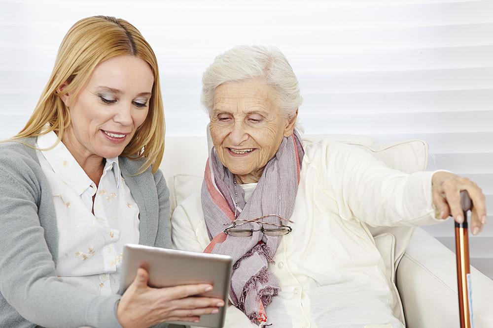 Kvinna ger instruktioner till pensionär om internet