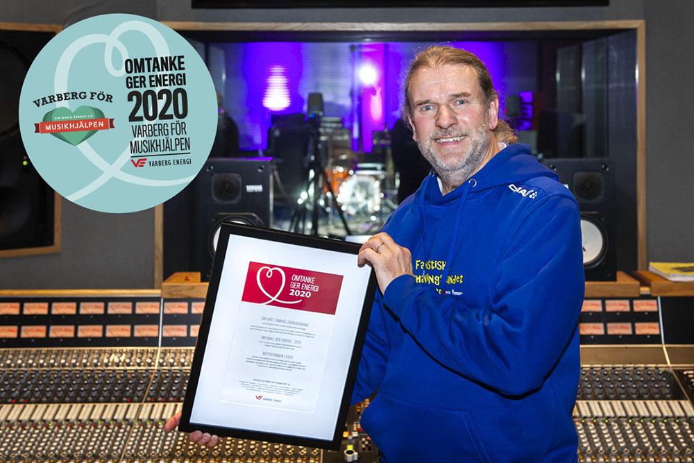 Calle Karlsson står framför en musikstudios kontrollbord med priset, tavlan, i handen