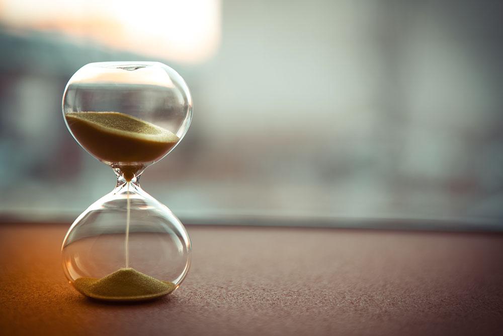 timglas ensamt på bord med suddig bakgrund