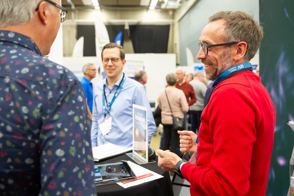 Rödklädd kollega pratar glatt med en intresserad besökare på mässa och tittar på informtion i läsplatta.