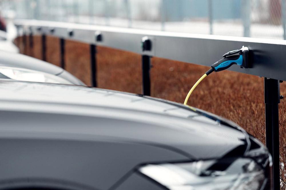 bilar står parkerade på rad framför elladdniongsbalk med eluttag