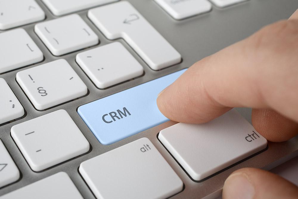 Tangentbord och ett finger som trycker på en knapp med texten CRM