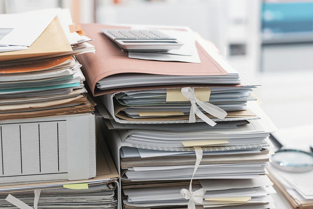 arkiv med massor av papper ligger travade på ett bord