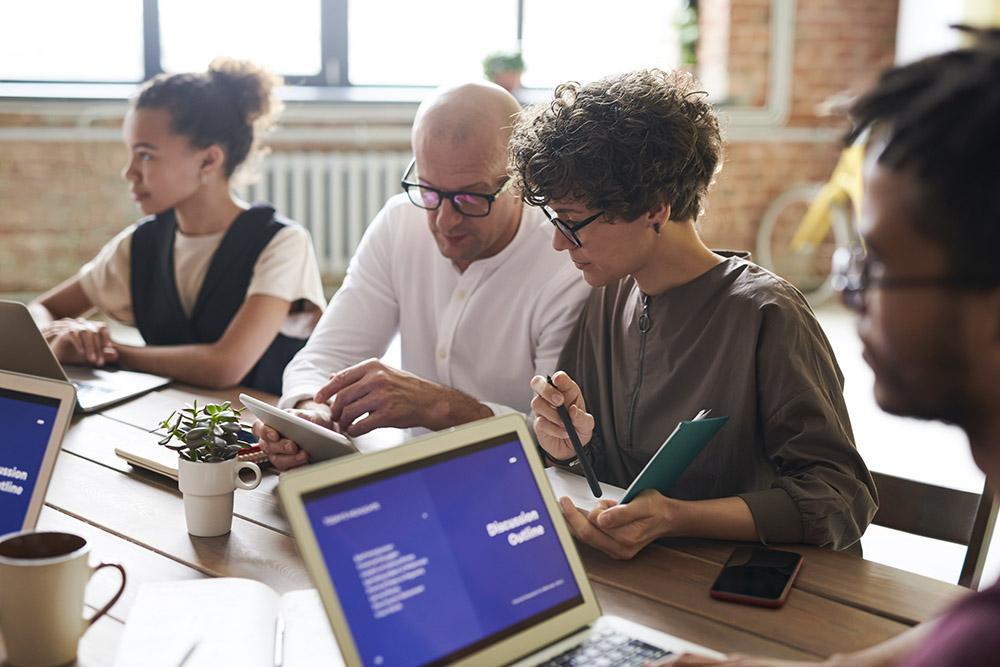 Kvinnor och män i olika åldrar oh etniciteter sitter vid ett bord och arbetar vid laptops och hjälper varandra