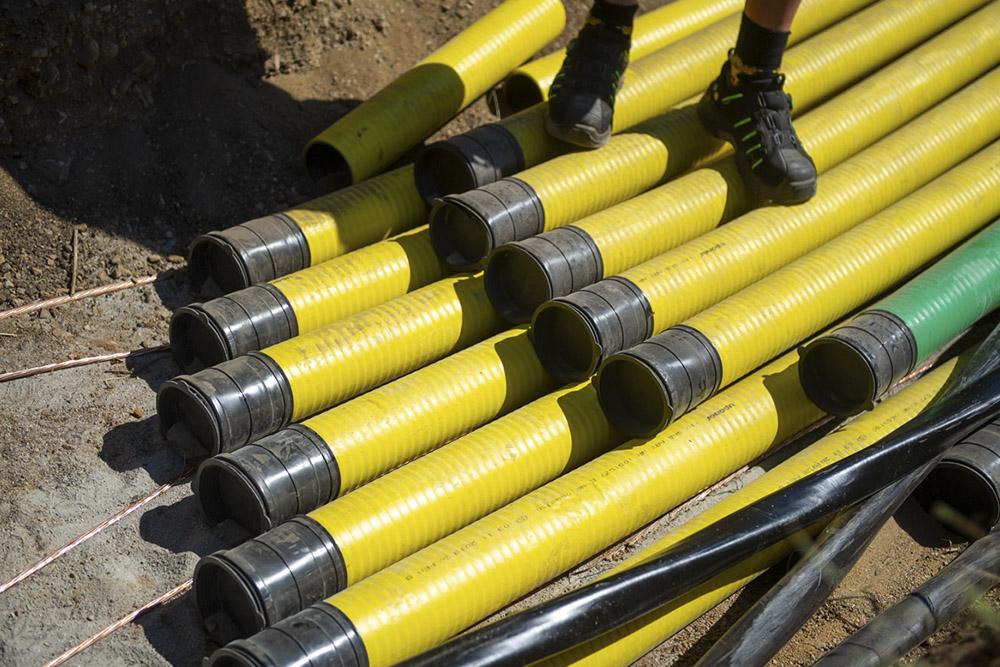 ett flertal gula kabelrör i botten av ett grävt schakt