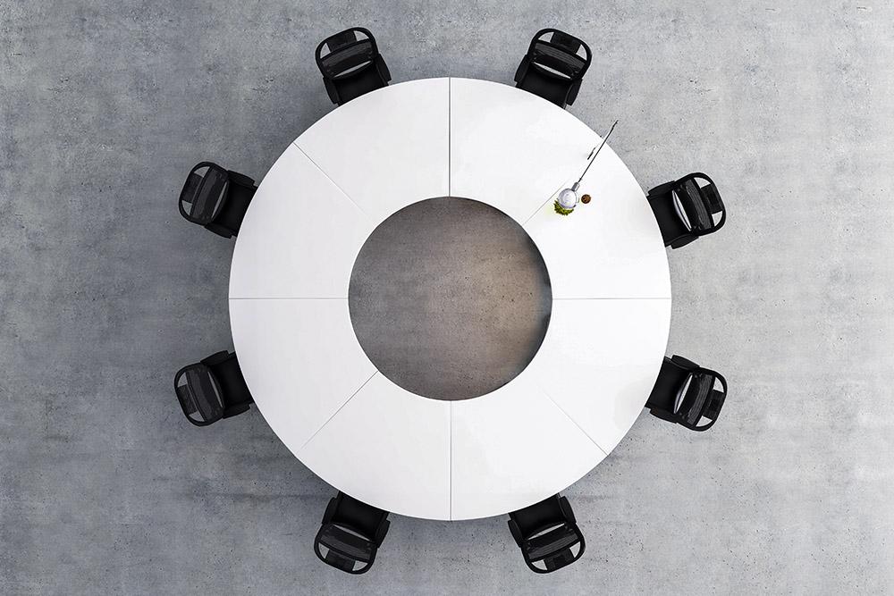 vitt runt bord med hål i mitten med svarta stolar sett uppifrån