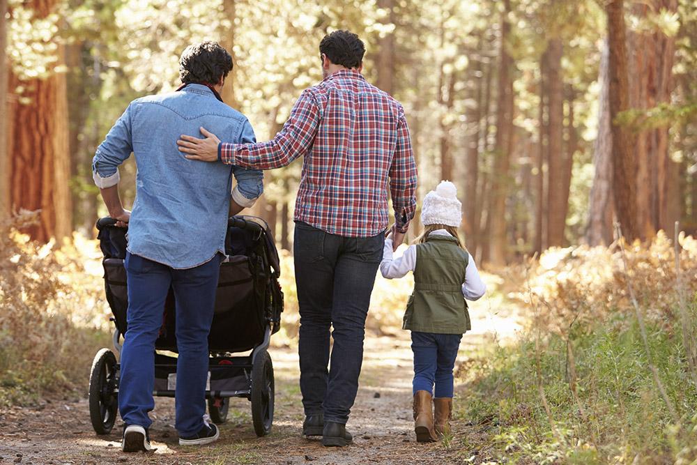 ett par män går i skogen tillsammans med sina barn