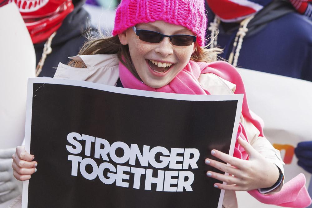 flicka med solglasögon och rosa toppluva håller upp skylt med text Stronger together