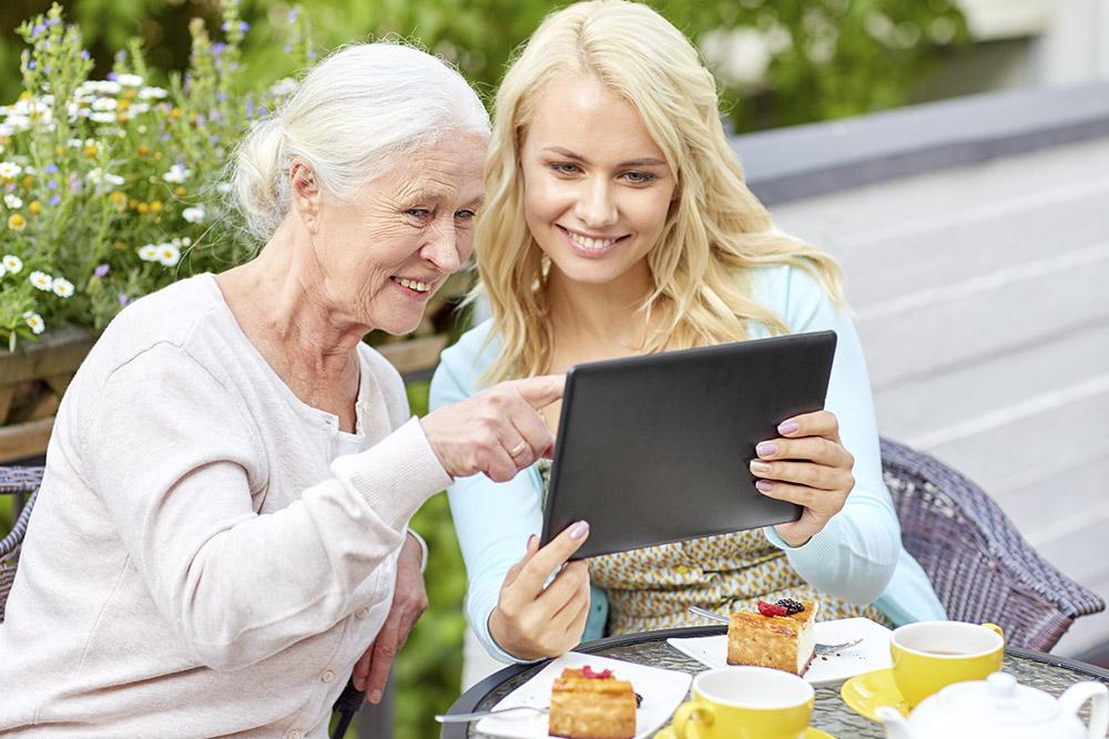 Ung kvinna sitter och fikar med gammal kvinna och de tittar tillsammans på en läsplatta