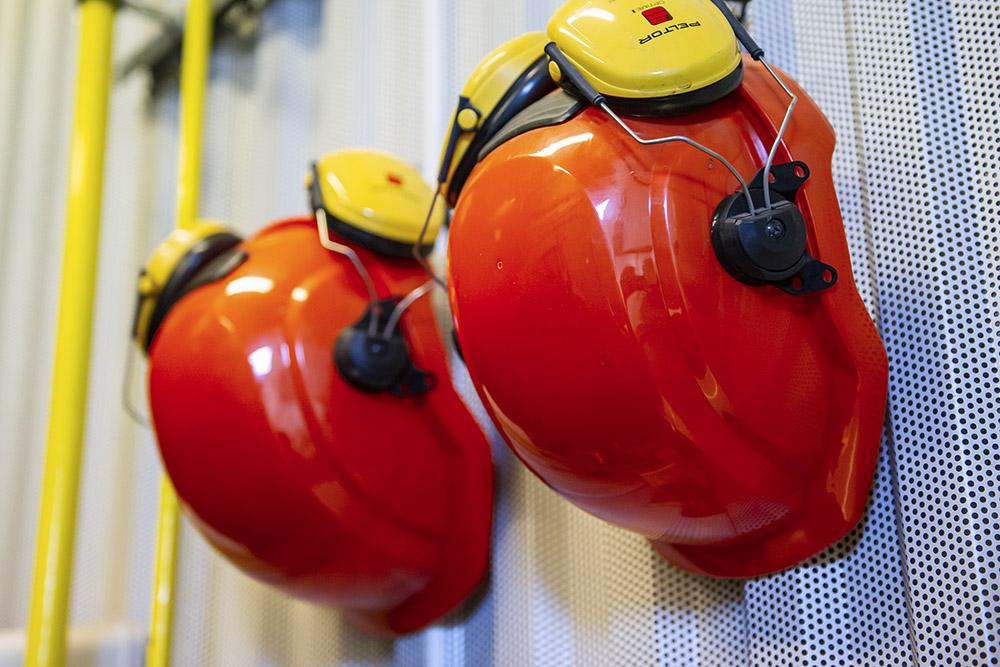 två röda hjälmar med gula hörselkåpor hänger på plåtvägg